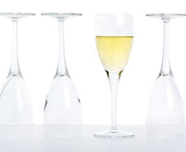 Image of Four Glasses. Three turned upside down and one full with champange